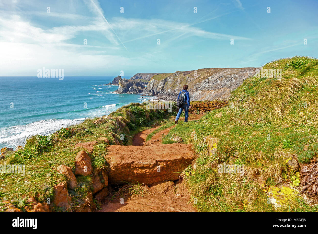 A woman walking towards Pentreath beach on the South west Coast path, Lizard Point, Cornwall, South West, England, - Stock Image