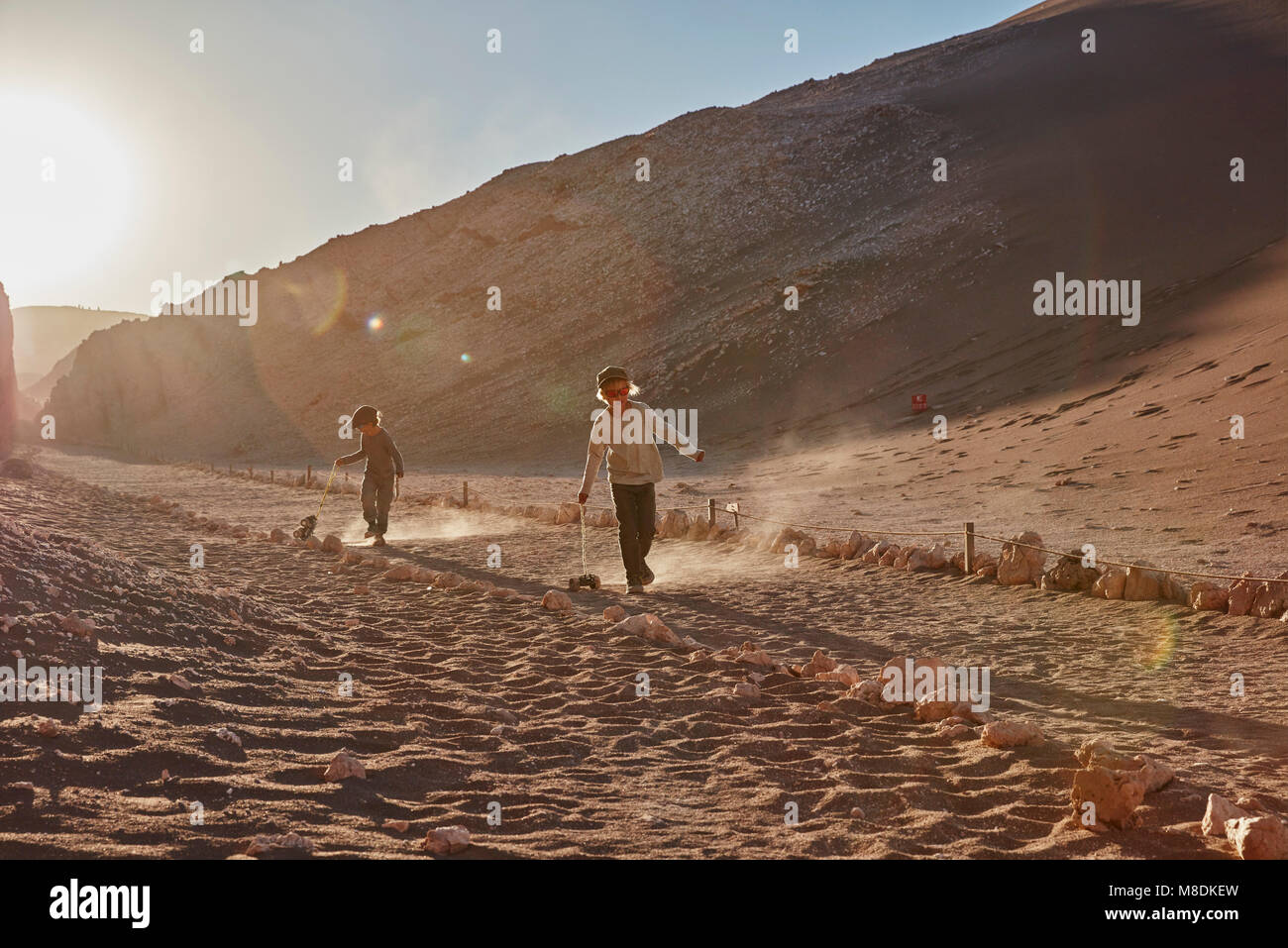 Boy and his brother pulling toy trucks along desert path, Atacama, Chile - Stock Image