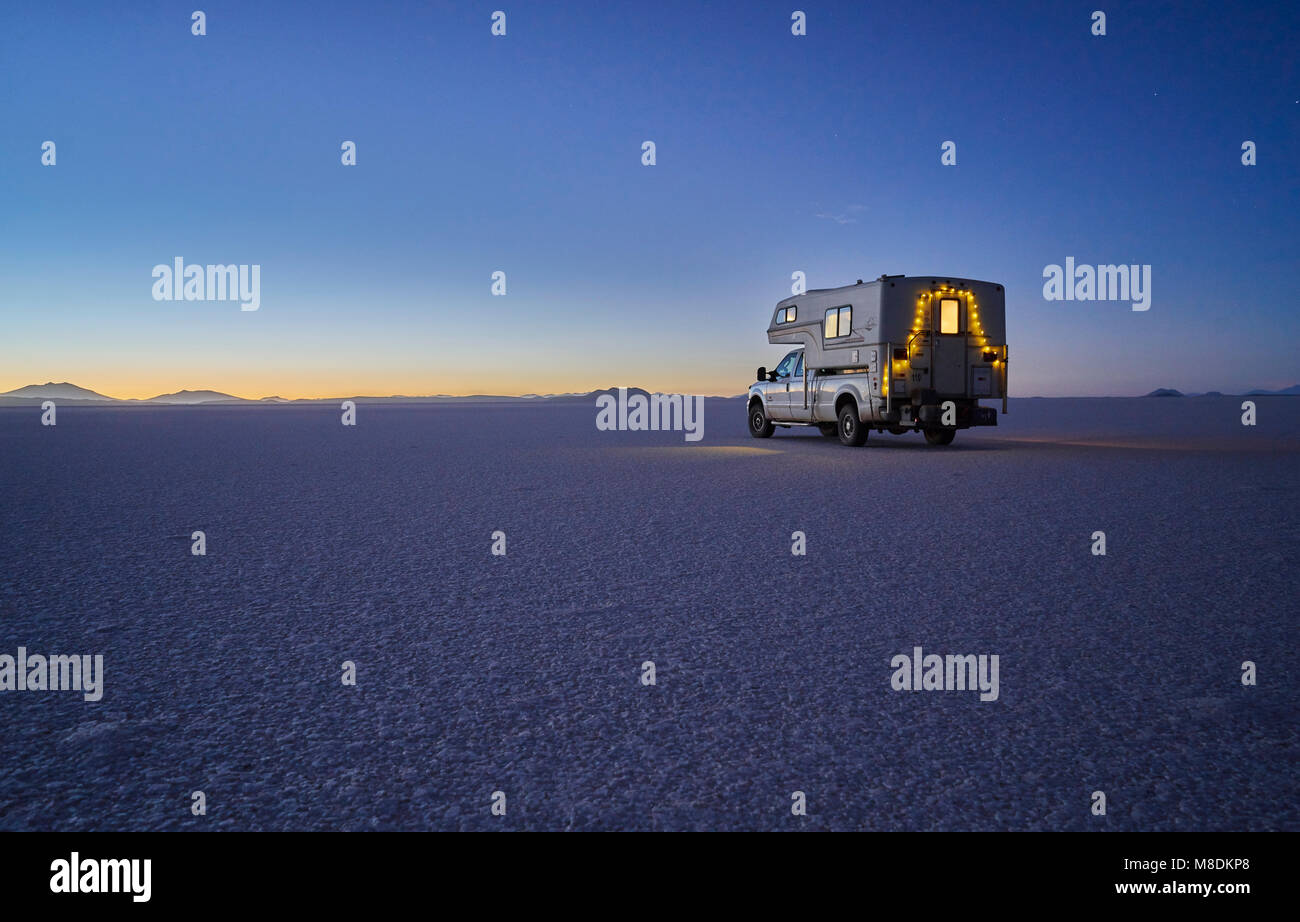 Recreational vehicle, travelling at dusk, across salt flats, Salar de Uyuni, Uyuni, Oruro, Bolivia, South America - Stock Image