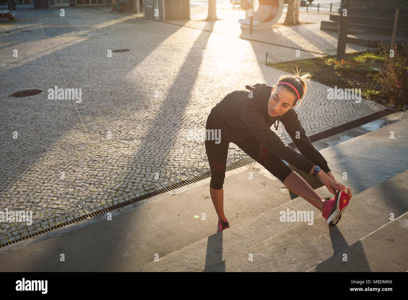Young woman warming up, stretching legs - Stock Image