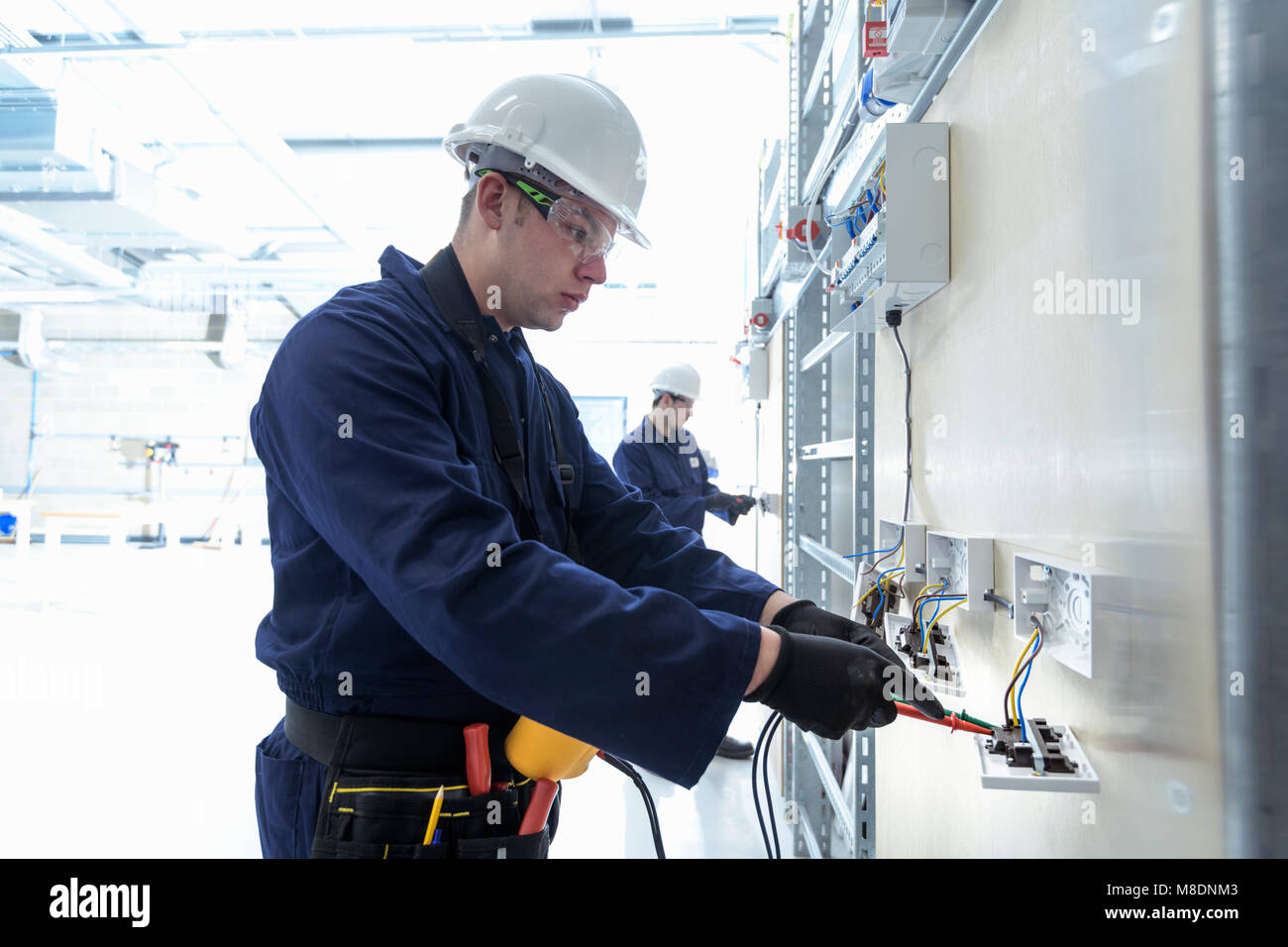 Electrical engineers testing electrical equipment - Stock Image