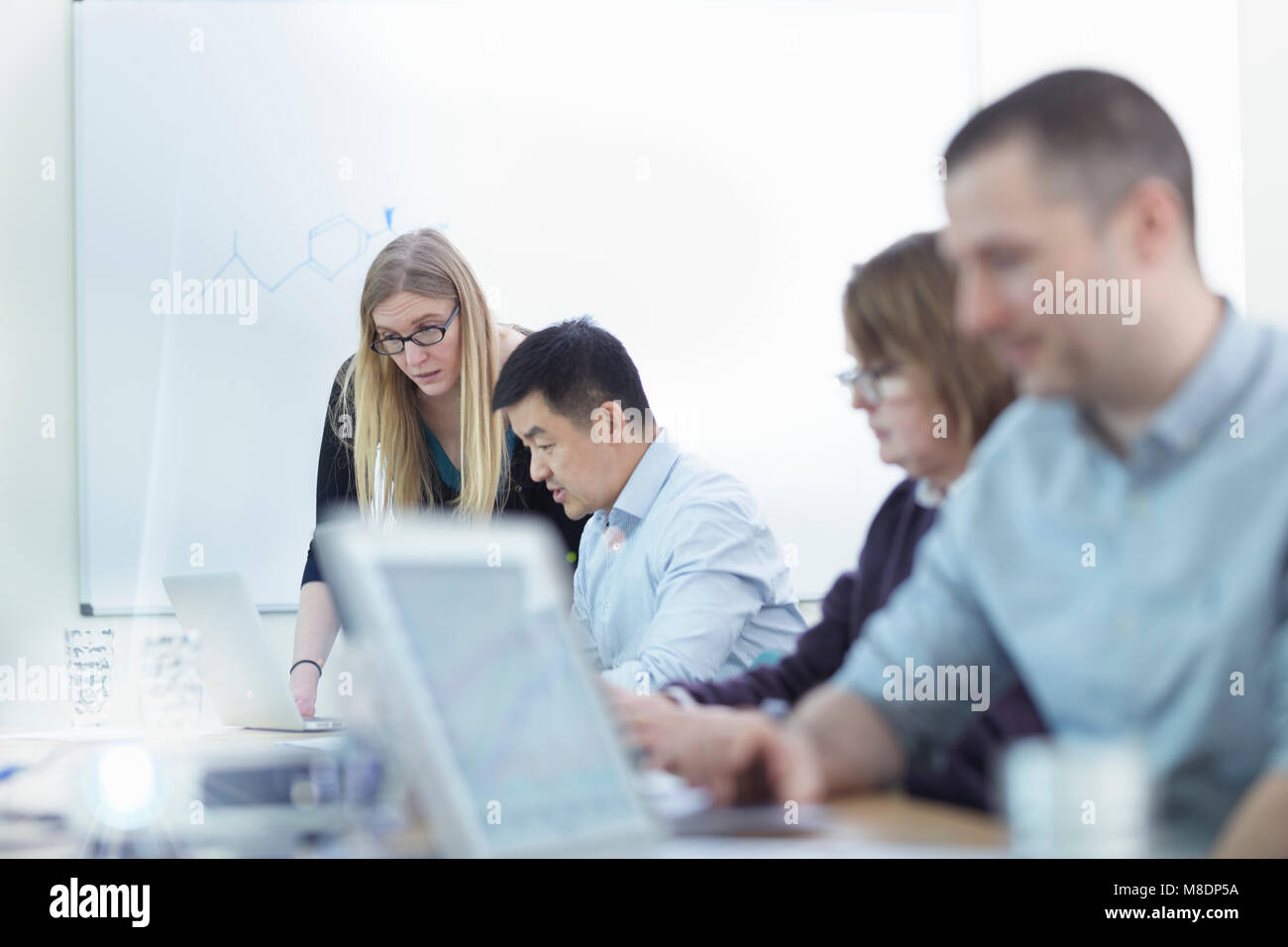 Younger and older scientists discussing pharmaceutical science project in meeting room - Stock Image