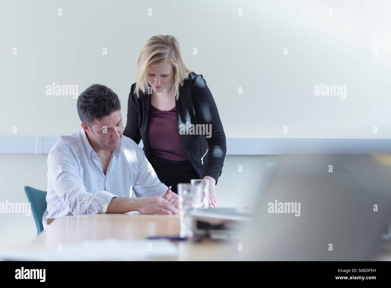Female and male scientists signing contract about pharmaceutical project in meeting room - Stock Image