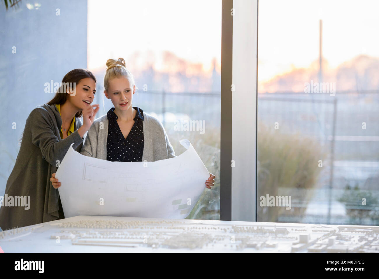 Colleagues discussing town planning drawings in office - Stock Image