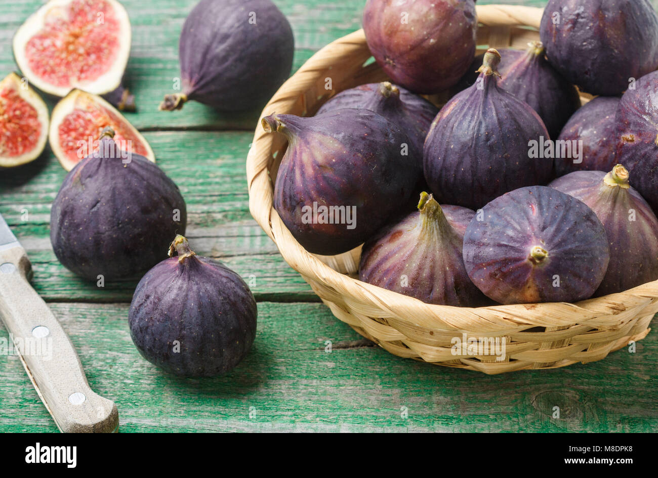Fresh ripe organic figs with drops of water on a wooden table. Selective focus - Stock Image