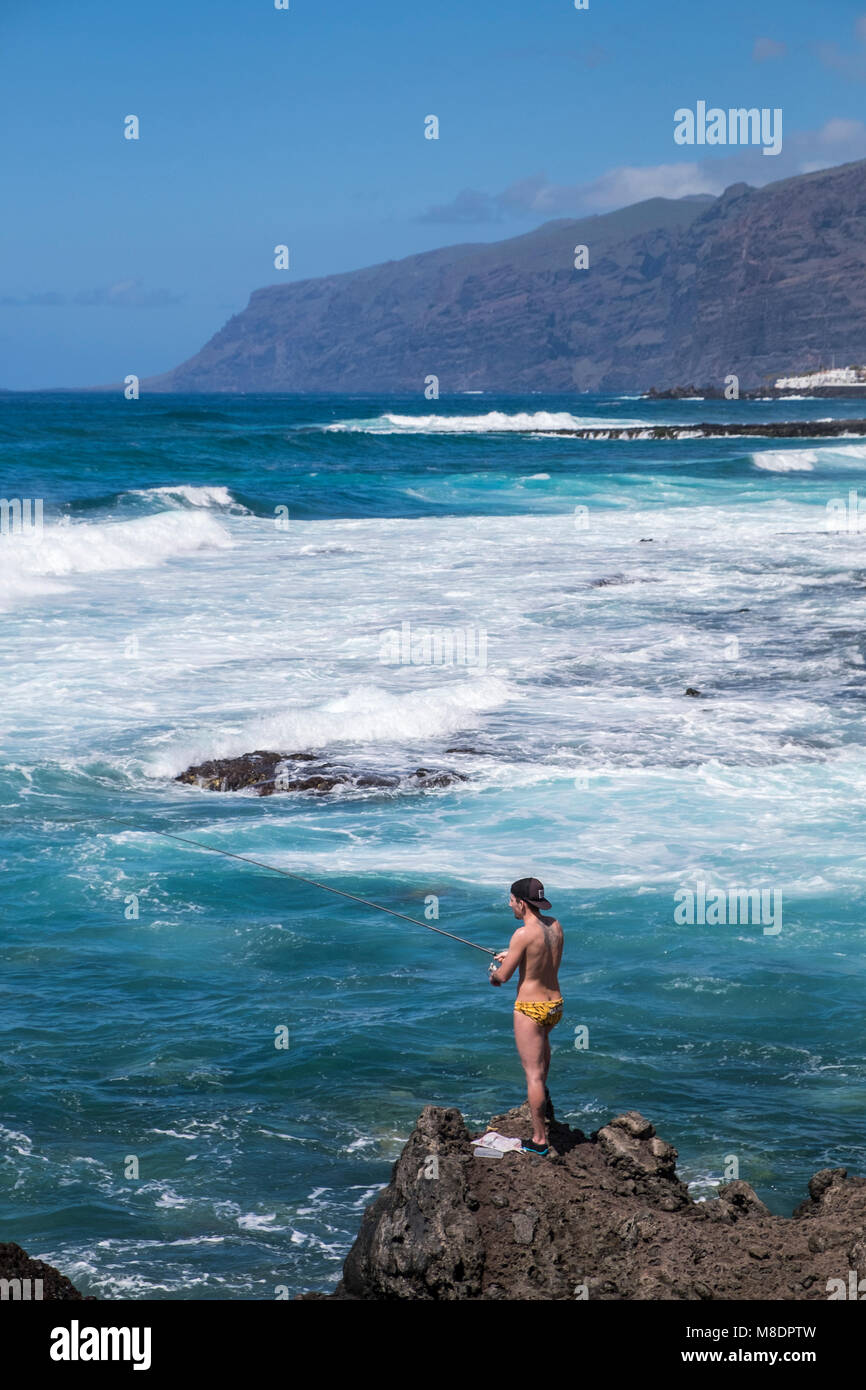 Youth fishing off rocks wearing swim trunks, hat and shoes, Alcala, with Los Gigantes cliffs in background, Tenerife, - Stock Image
