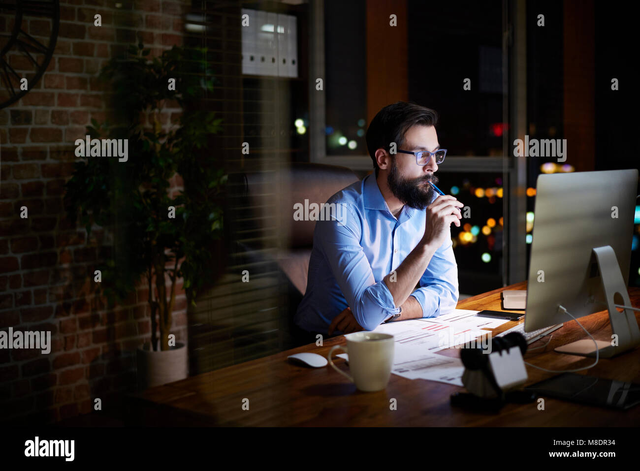 Young businessman looking at computer on office desk at night Stock Photo