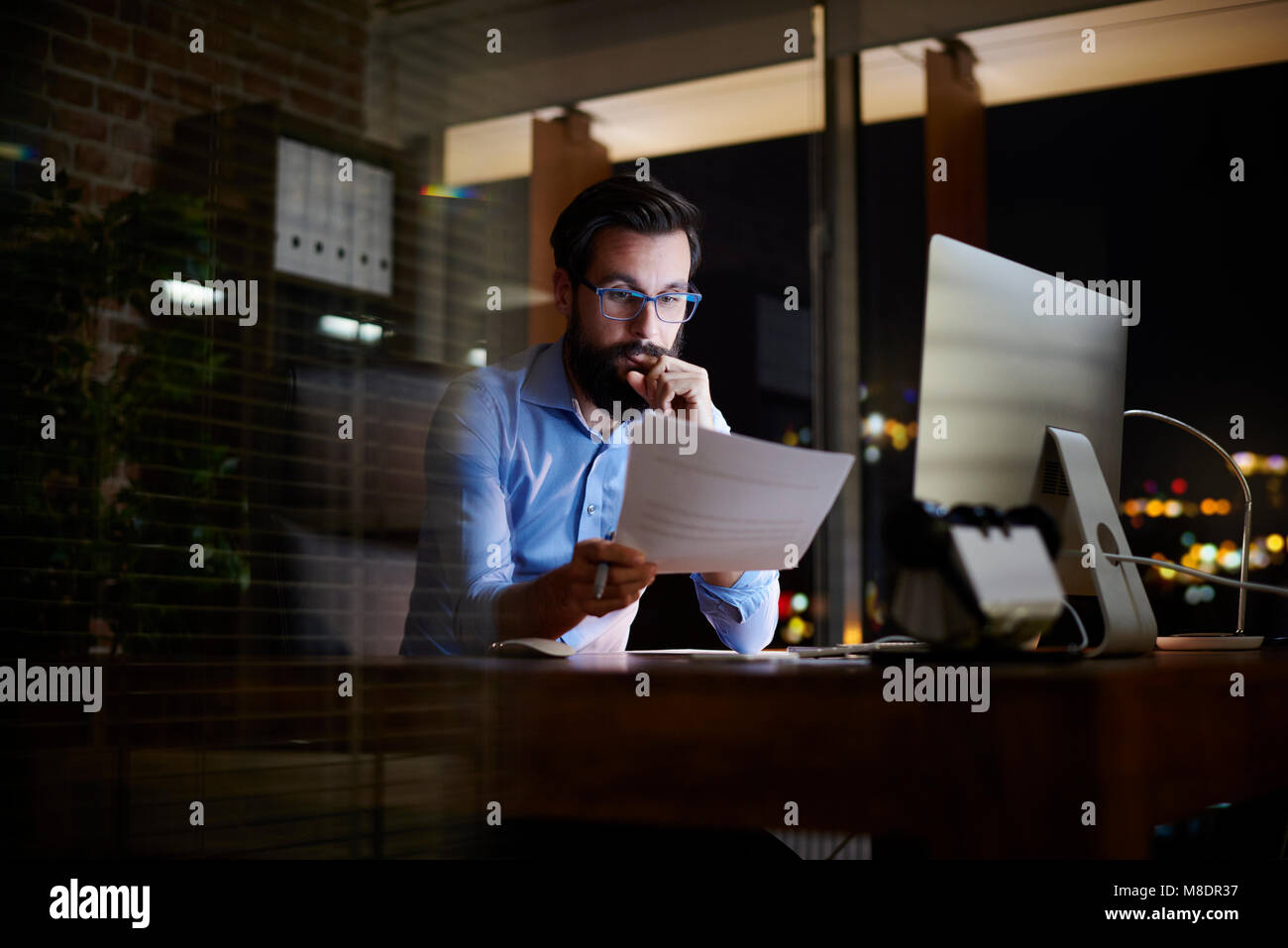 Young businessman reading paperwork at office desk at night - Stock Image