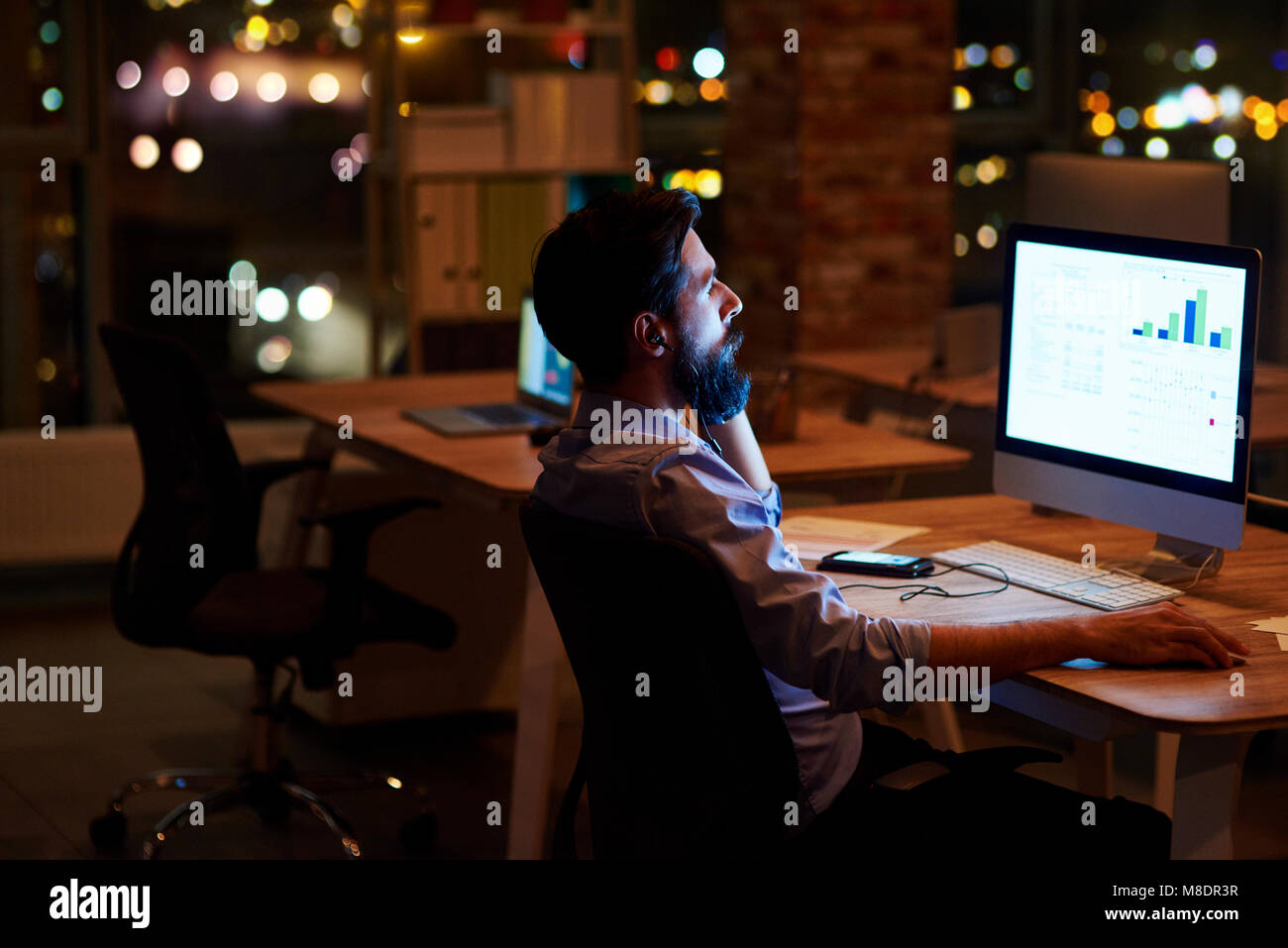 Young businessman looking at computer on office desk at night - Stock Image
