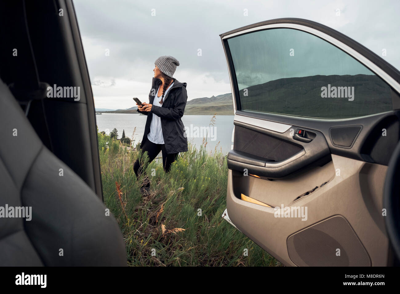 Young woman standing beside Dillon Reservoir, holding smartphone, view through parked car, Silverthorne, Colorado, - Stock Image