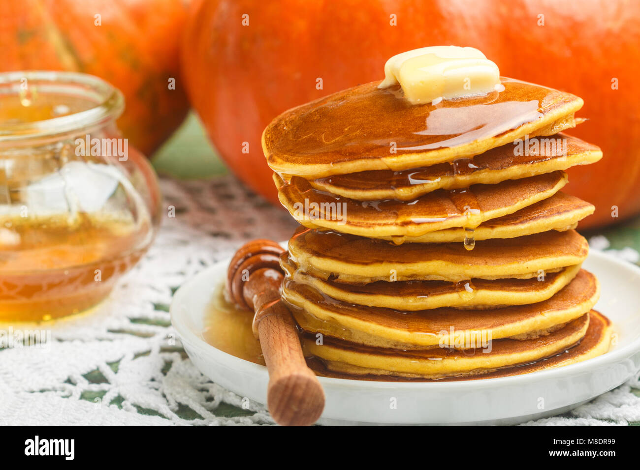 Homemade pumpkin pancakes with butter and honey on a white plate on the table. Useful, tasty Breakfast. Selective - Stock Image