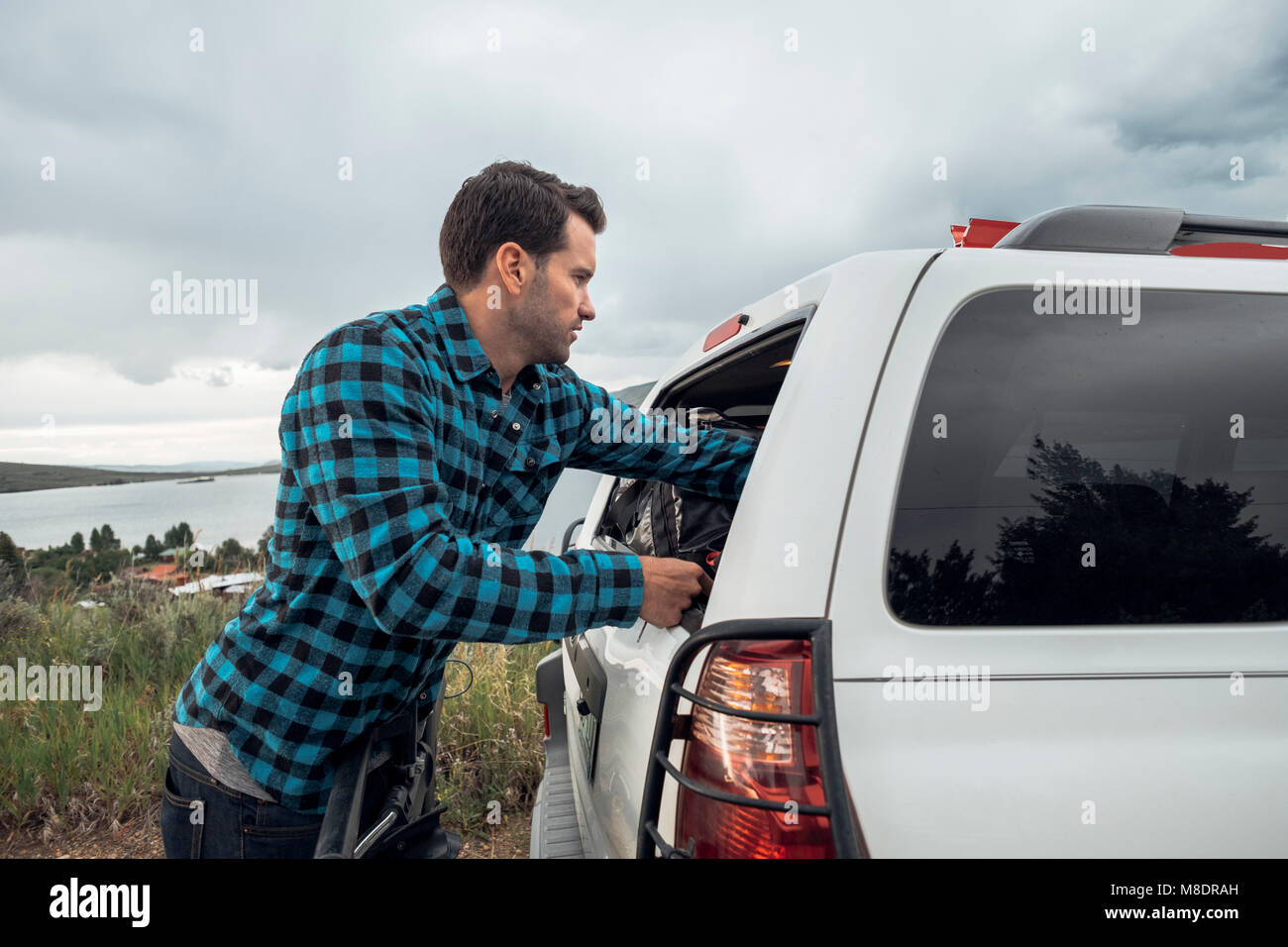 Mid adult man reaching into window of parked car, Silverthorne, Colorado, USA Stock Photo
