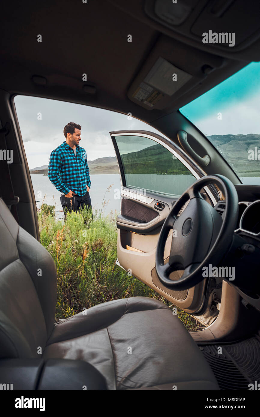 Mid adult man standing beside Dillon Reservoir, view through parked car, Silverthorne, Colorado, USA - Stock Image