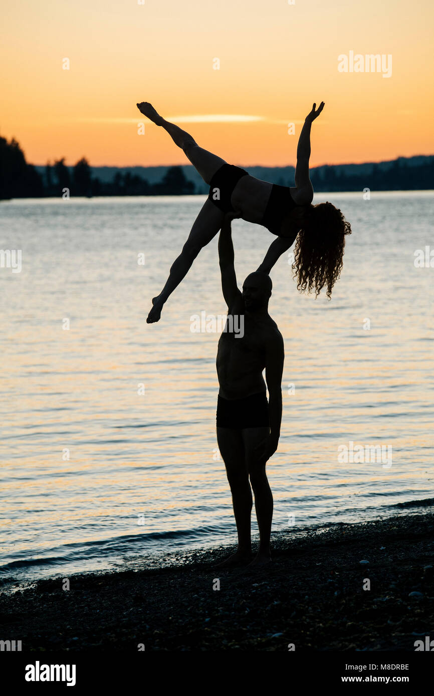 Couple practising yoga on beach at sunset - Stock Image