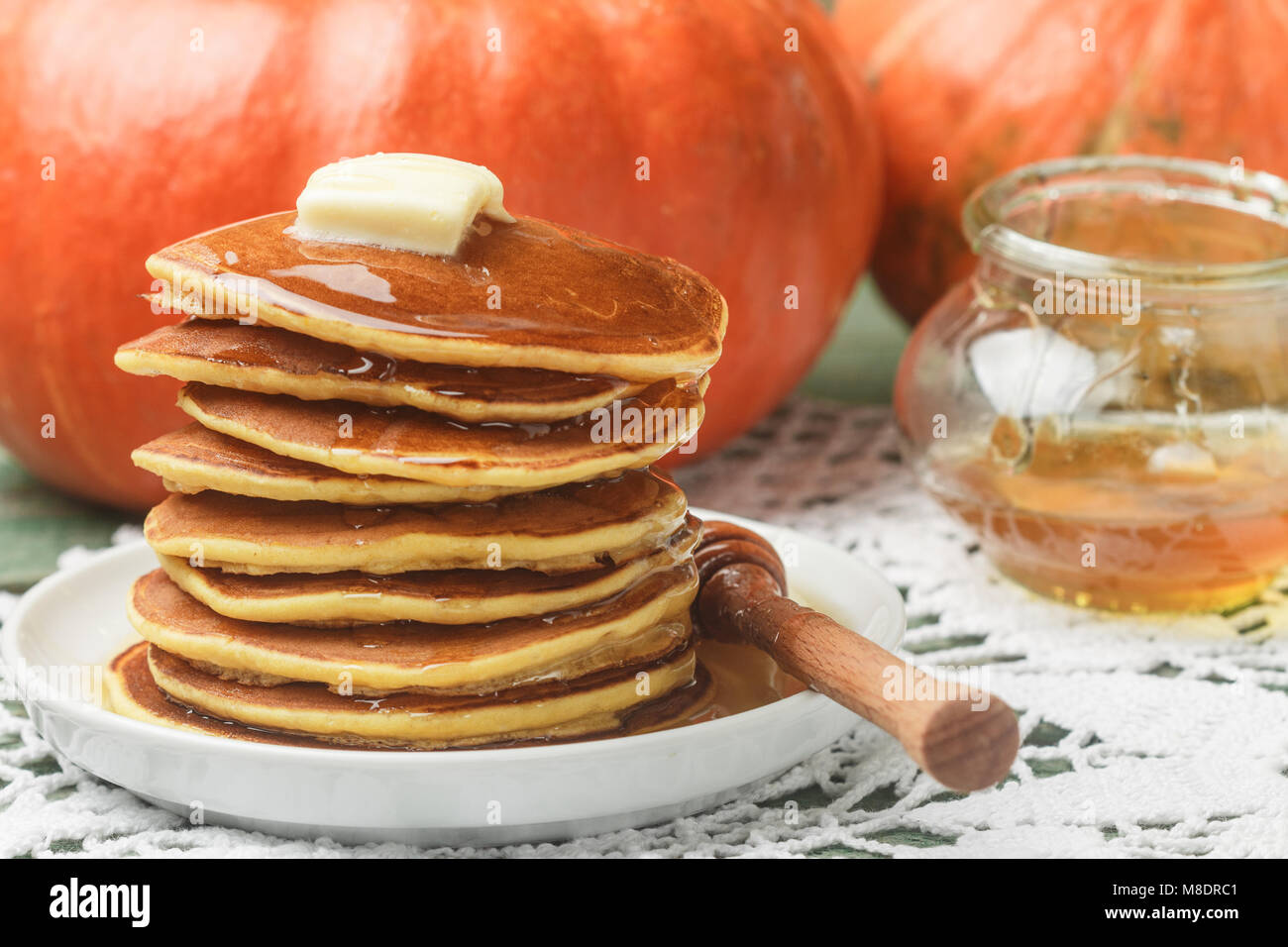 Homemade pumpkin pancakes with butter and honey on a white plate on the table. Useful, tasty Breakfast. Selective Stock Photo