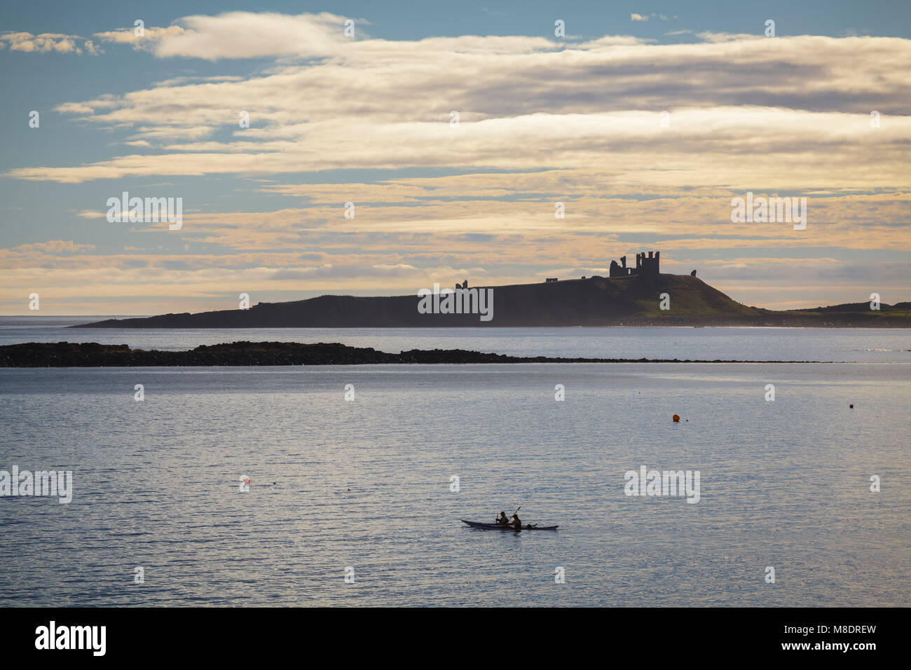 Dunstanburgh Castle and two Kayakers, Northumberland - Stock Image