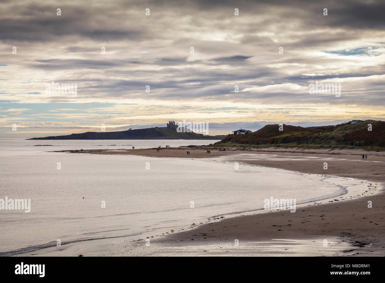 Dunstanburgh Castle and Low Newton-by-the-Sea in Northumberland - Stock Image