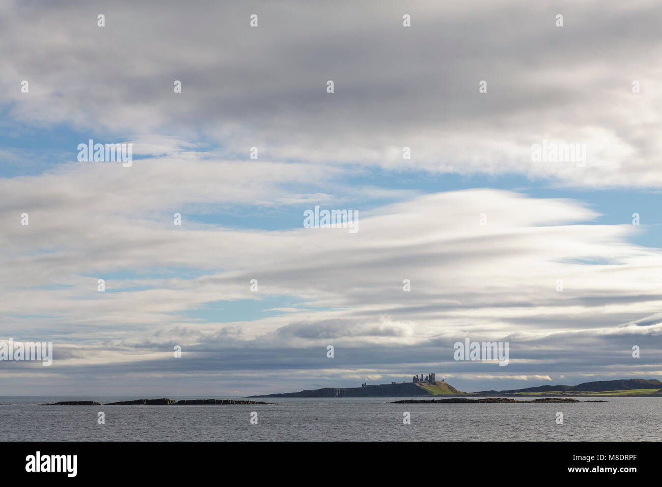 Dunstanburgh Castle and big skies Northumberland Stock Photo