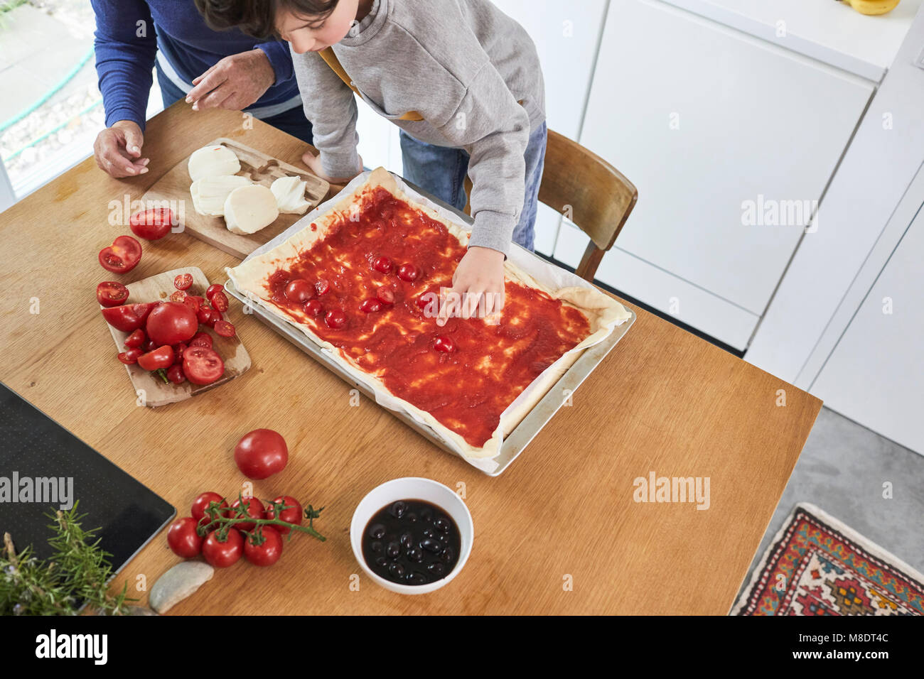 Grandmother and grandson making pizza in kitchen, elevated view - Stock Image