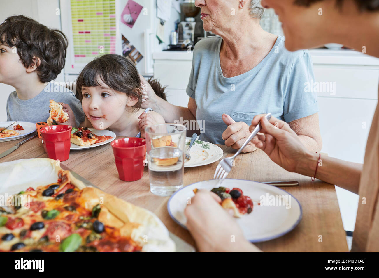 Three generation family sitting at kitchen table eating pizza - Stock Image