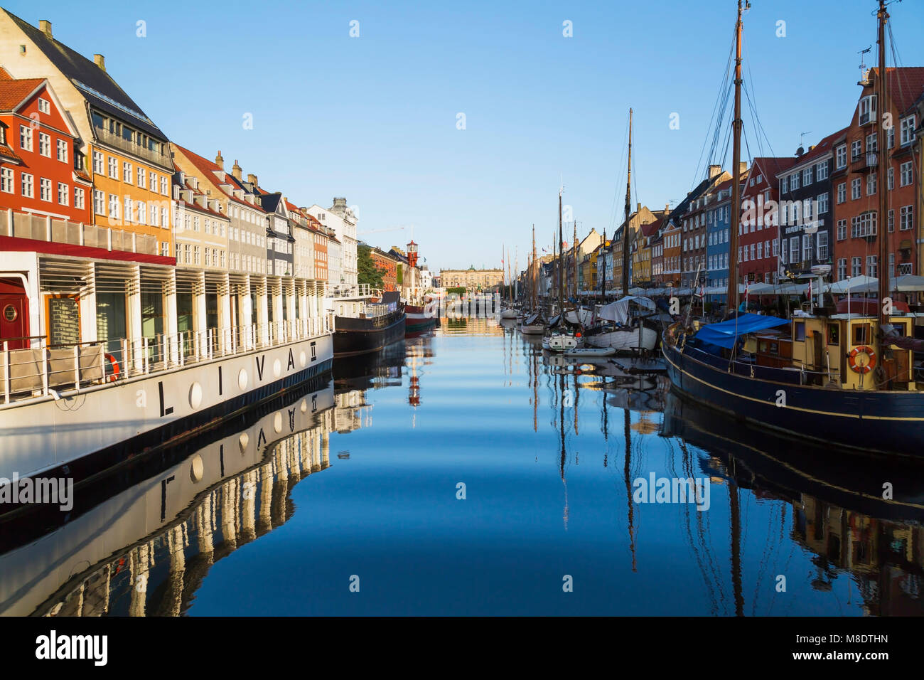 Moored restaurant boat and colourful 17th century town houses on Nyhavn canal, Copenhagen, Denmark - Stock Image