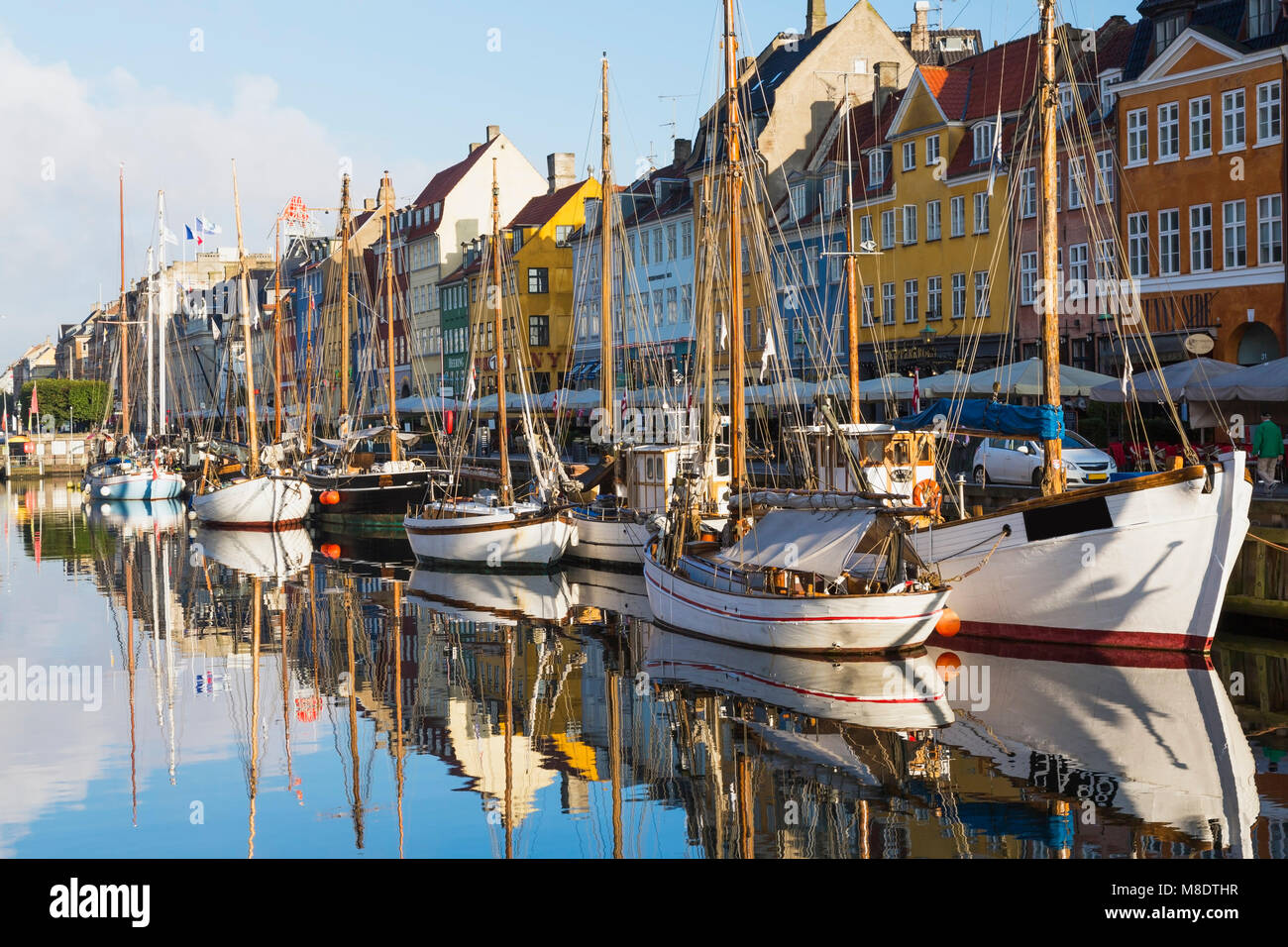 Moored boats and colourful 17th century town houses on Nyhavn canal, Copenhagen, Denmark - Stock Image