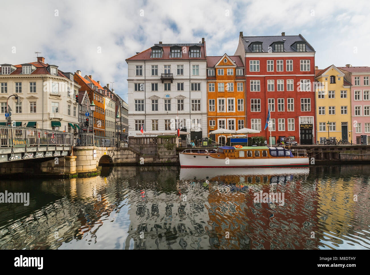 Moored boat and bridge with colourful 17th century town houses on Nyhavn canal, Copenhagen, Denmark - Stock Image