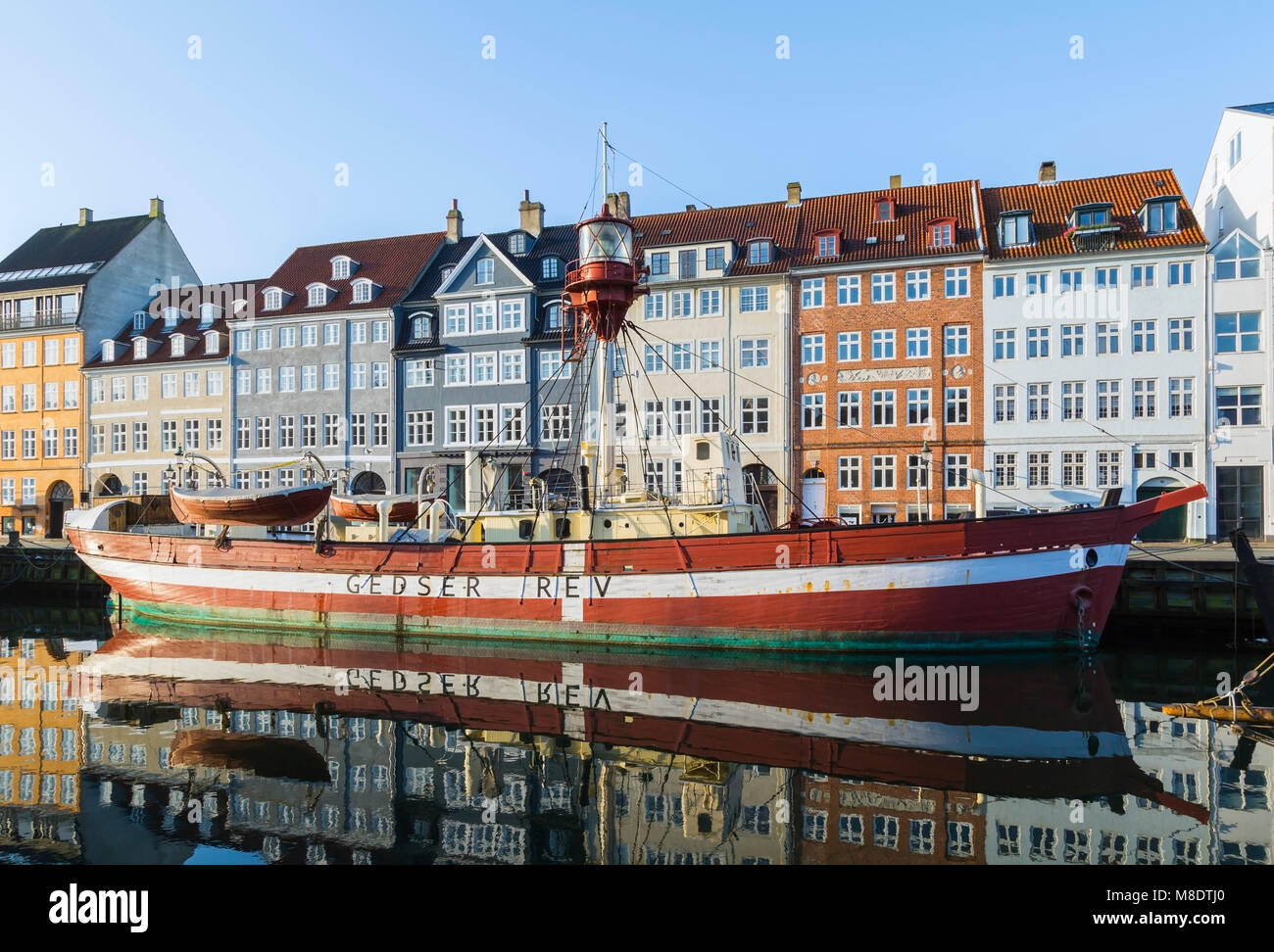 Moored boat with 17th century town houses on Nyhavn canal, Copenhagen, Denmark - Stock Image