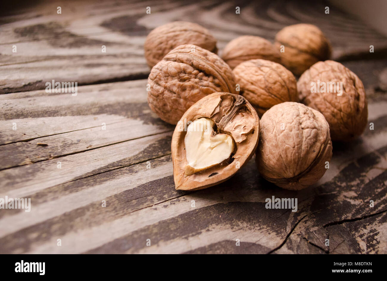 Walnuts on a grey textured wooden table. Assortment of nuts isolated on rustic old wooden background and splintered - Stock Image
