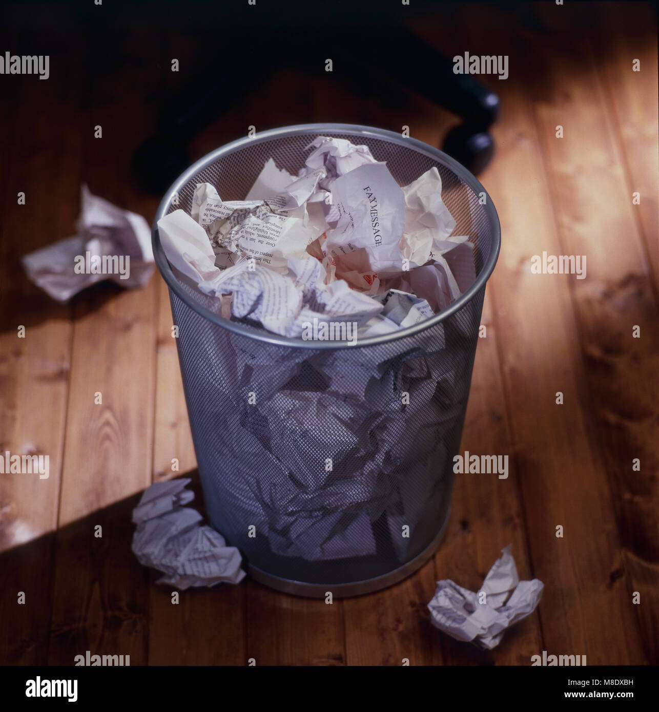 Office waste bin full of wastepaper - Stock Image