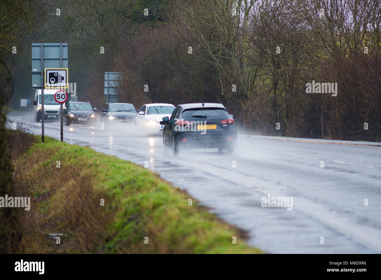 cars driving along water logged road with spray and rain and camera and 50 mph speed warning sign - Stock Image