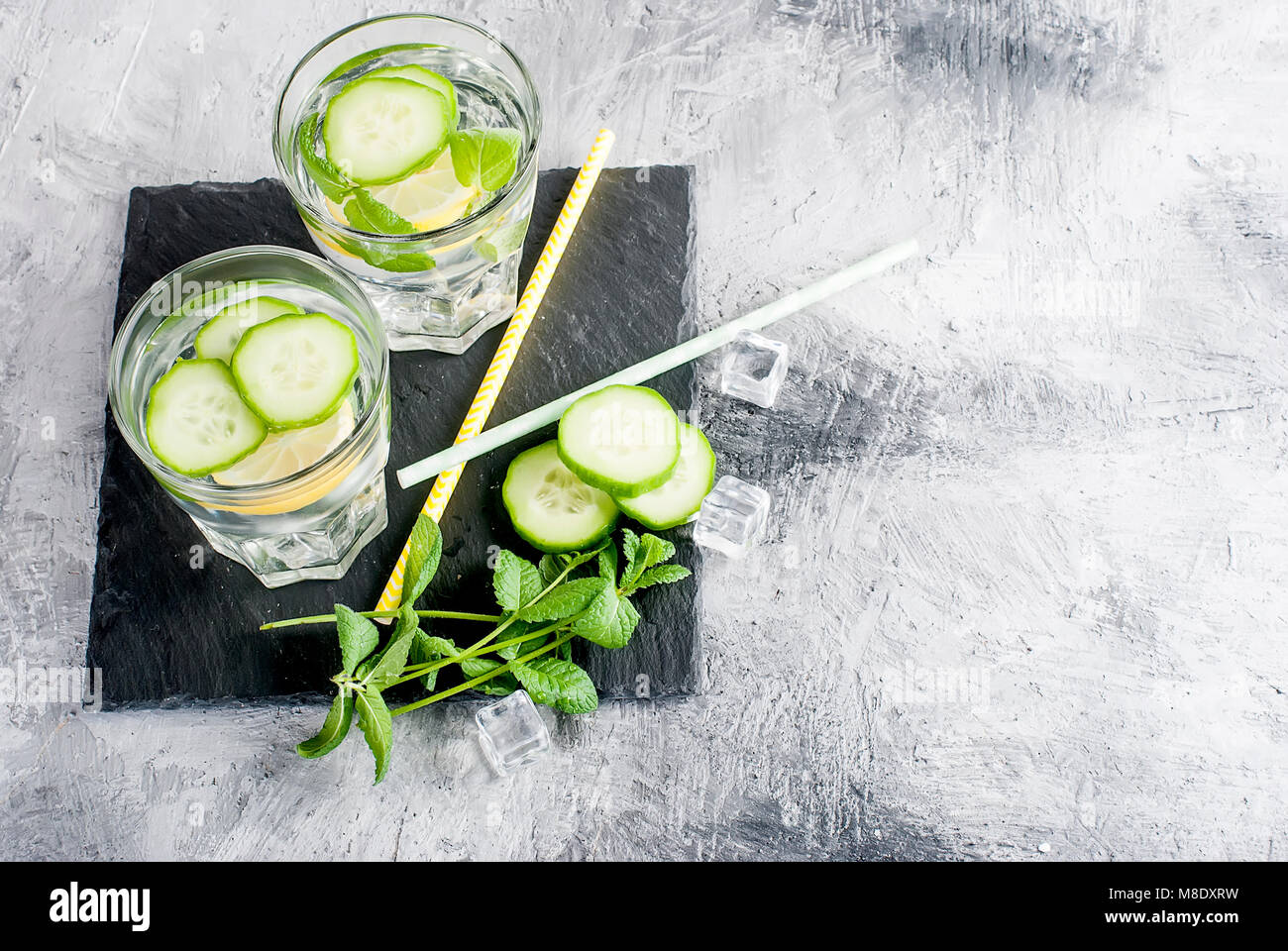 Refreshing cucumber cocktail, lemonade, detox water in a two glasses on a grey background. Summer drink. Top view Stock Photo