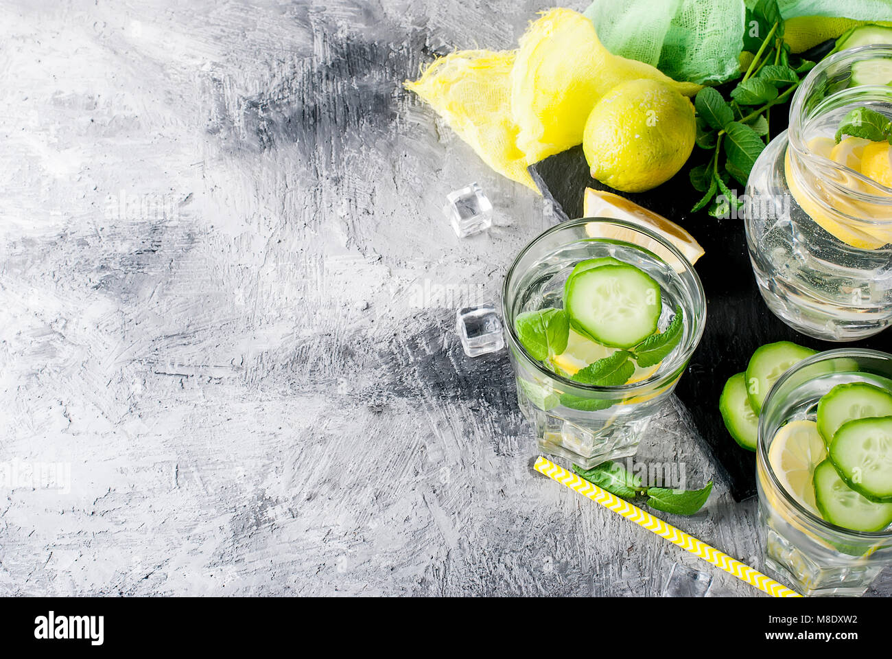 Refreshing cucumber cocktail, lemonade, detox water in a two glasses on a grey background. Summer drink. - Stock Image