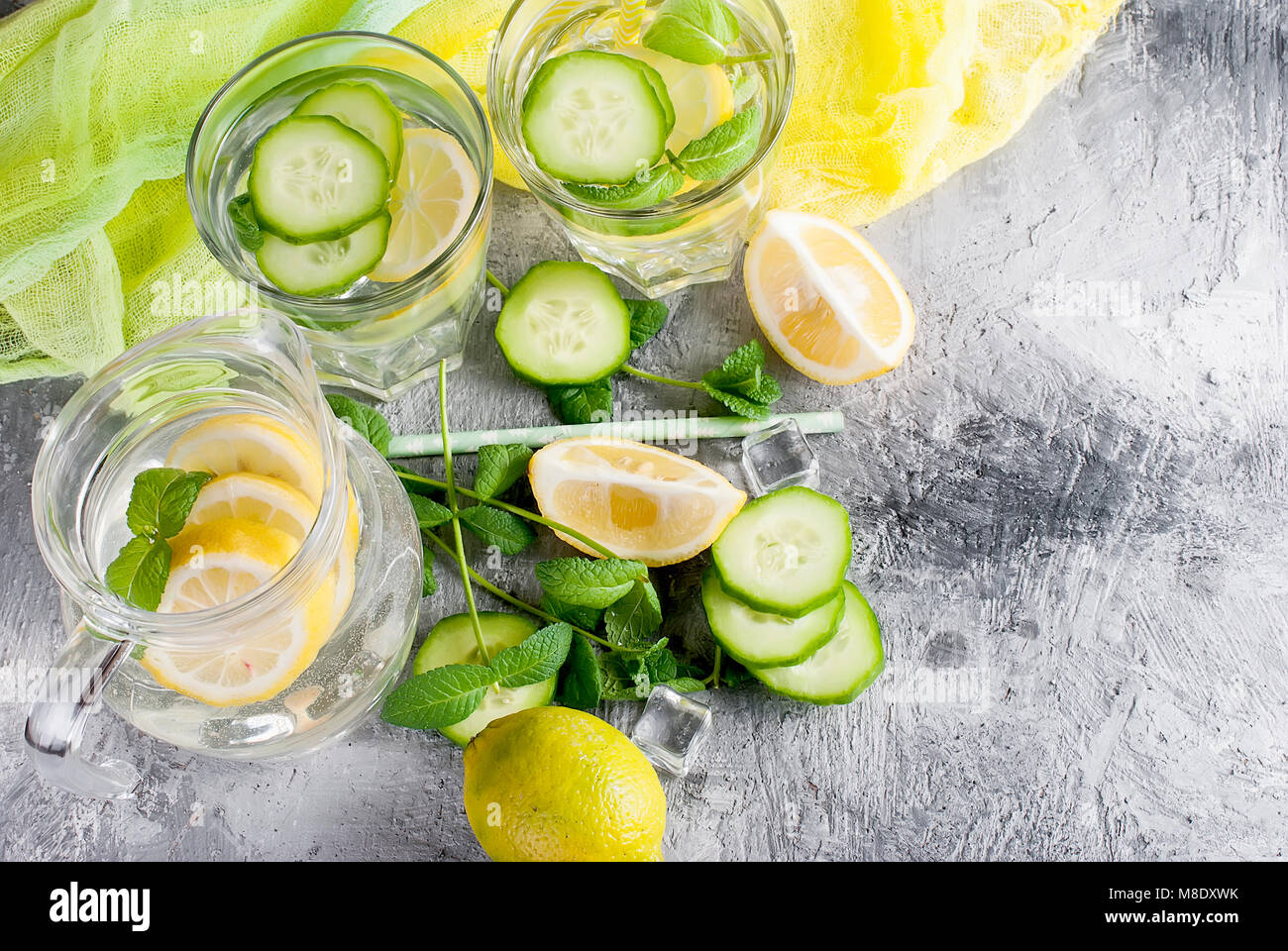 Citrus fruit and herbs infused sassi water for detox, healthy eating in  glasses and jug on over dark background - Stock Image