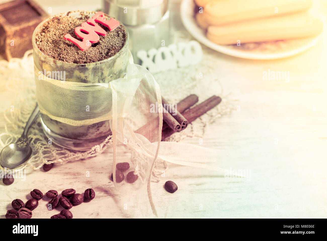 Tiramisu desert in round glass with lace ribbon, chocolate and silver spoon with letters word love. Copy space - Stock Image