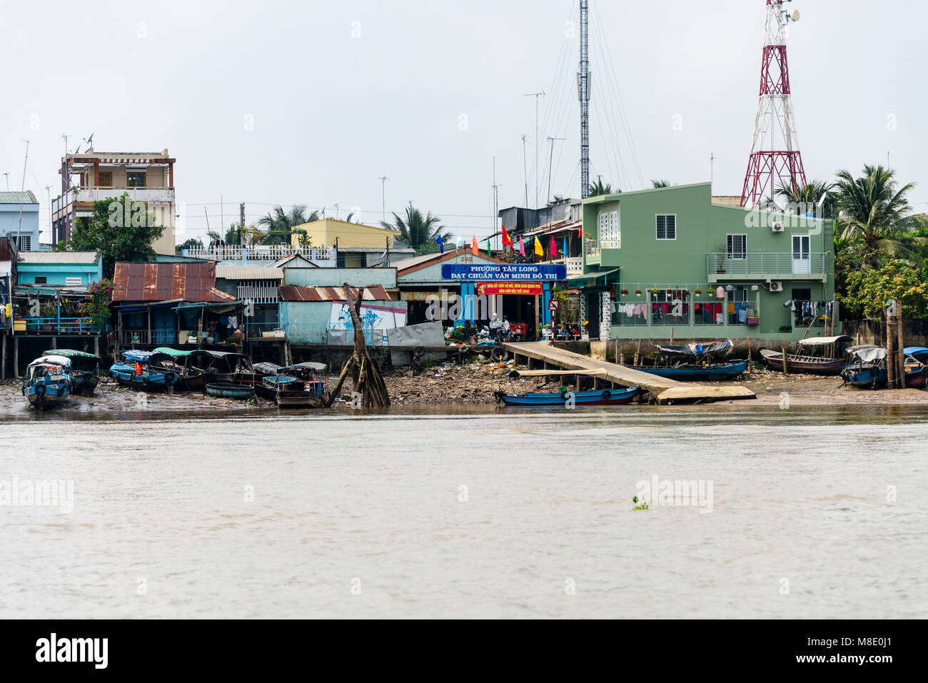 Boats, shops and makeshift houses on the bank of the Meekong River, Vietnam - Stock Image