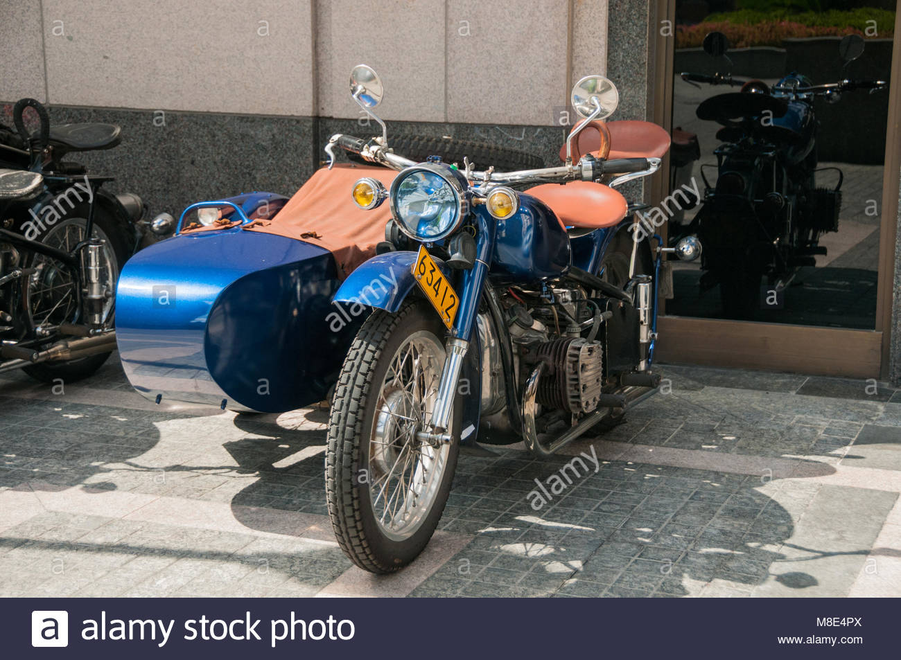 A gleaming blue Changjiang 750 motorcycle sidecar outside the Peninsula Hotel awaiting the start of a Shanghai Insiders - Stock Image