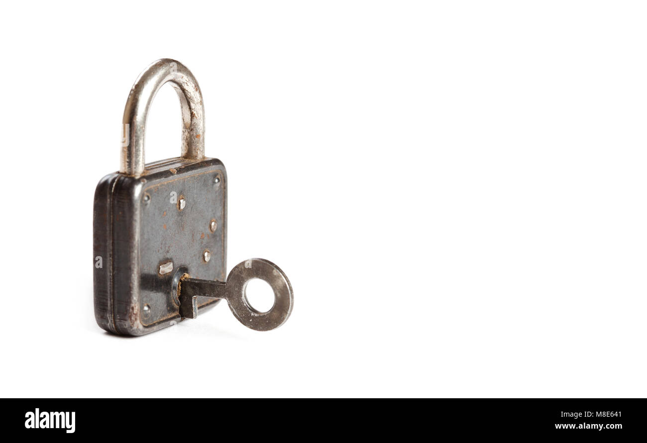 Vintage padlock with key in hole. hanging lock close-up. texture and detailed. white background - Stock Image