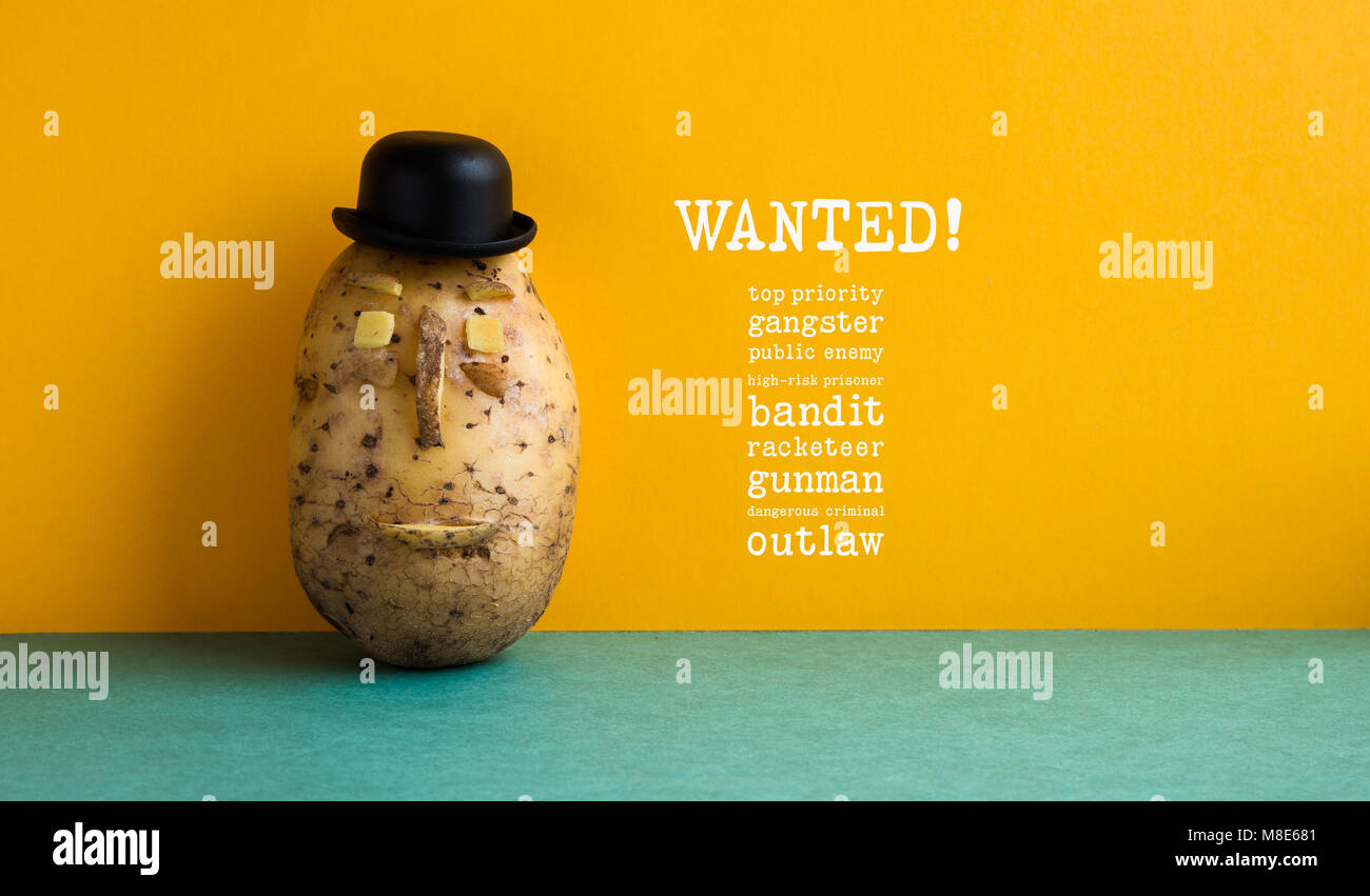 Wanted top priority potato gangster poster. Old fashioned style bowler black hat potato yellow wall, green floor. - Stock Image