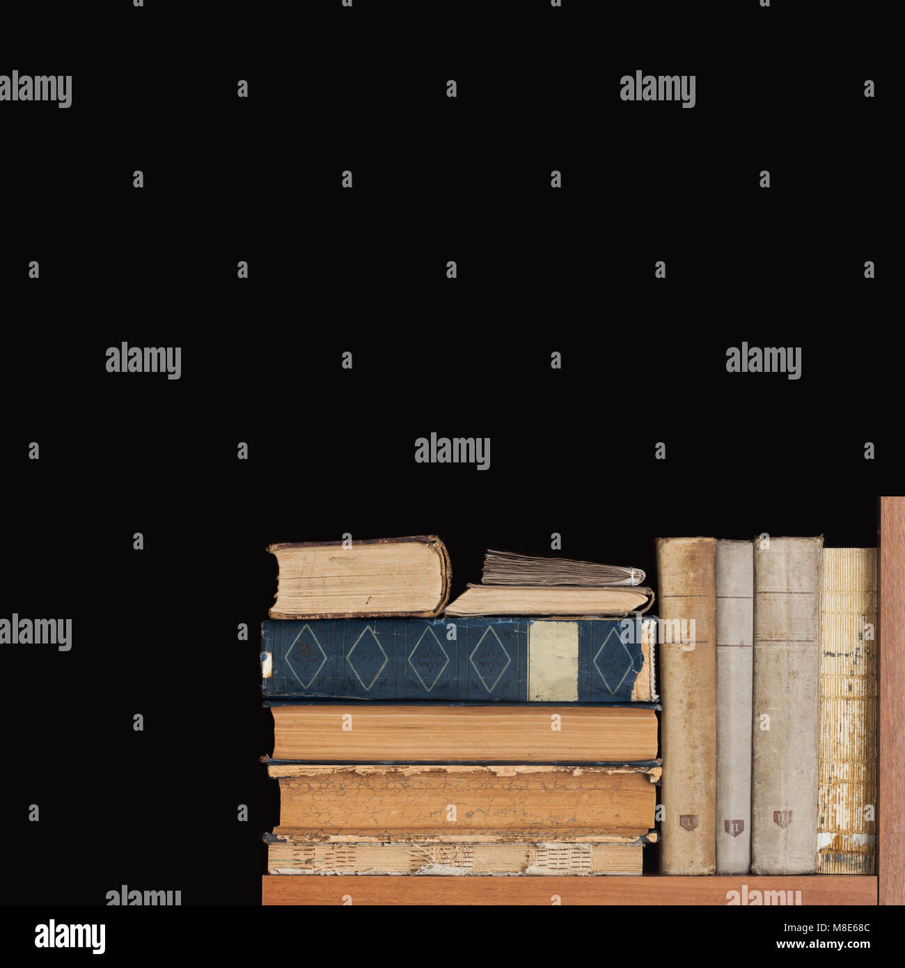 Book shelf on black background. Rare vintage library books collection, antique textured covers. aged wooden frame. - Stock Image