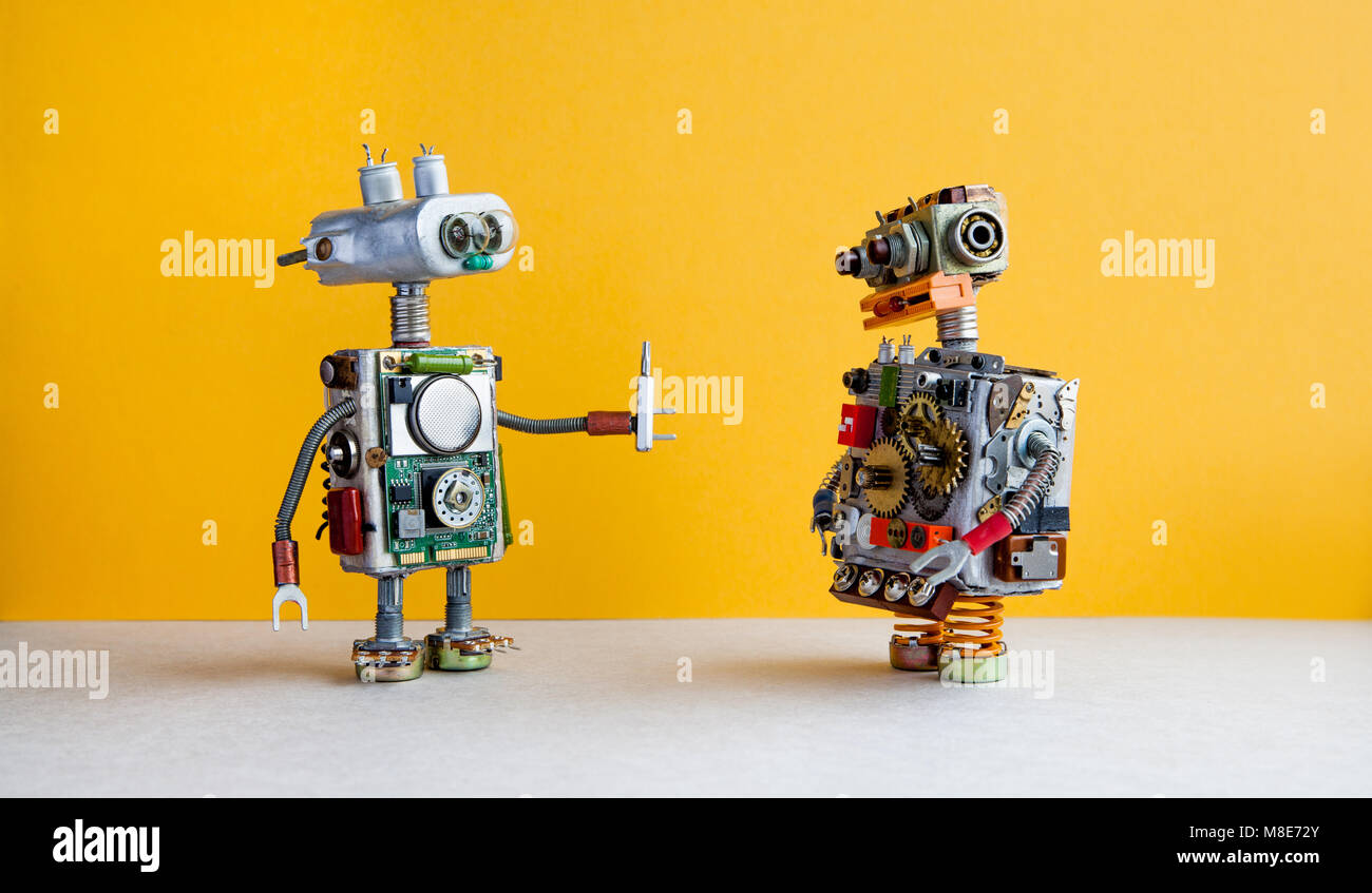 Robots on yellow background. 4th industrial revolution automation concept. Robotic serviceman with screwdriver, - Stock Image