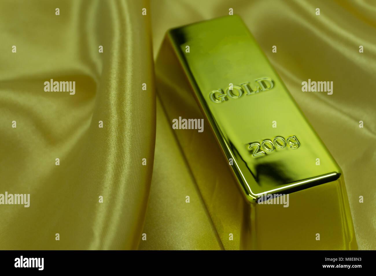 Gold ingot on the surface - Stock Image
