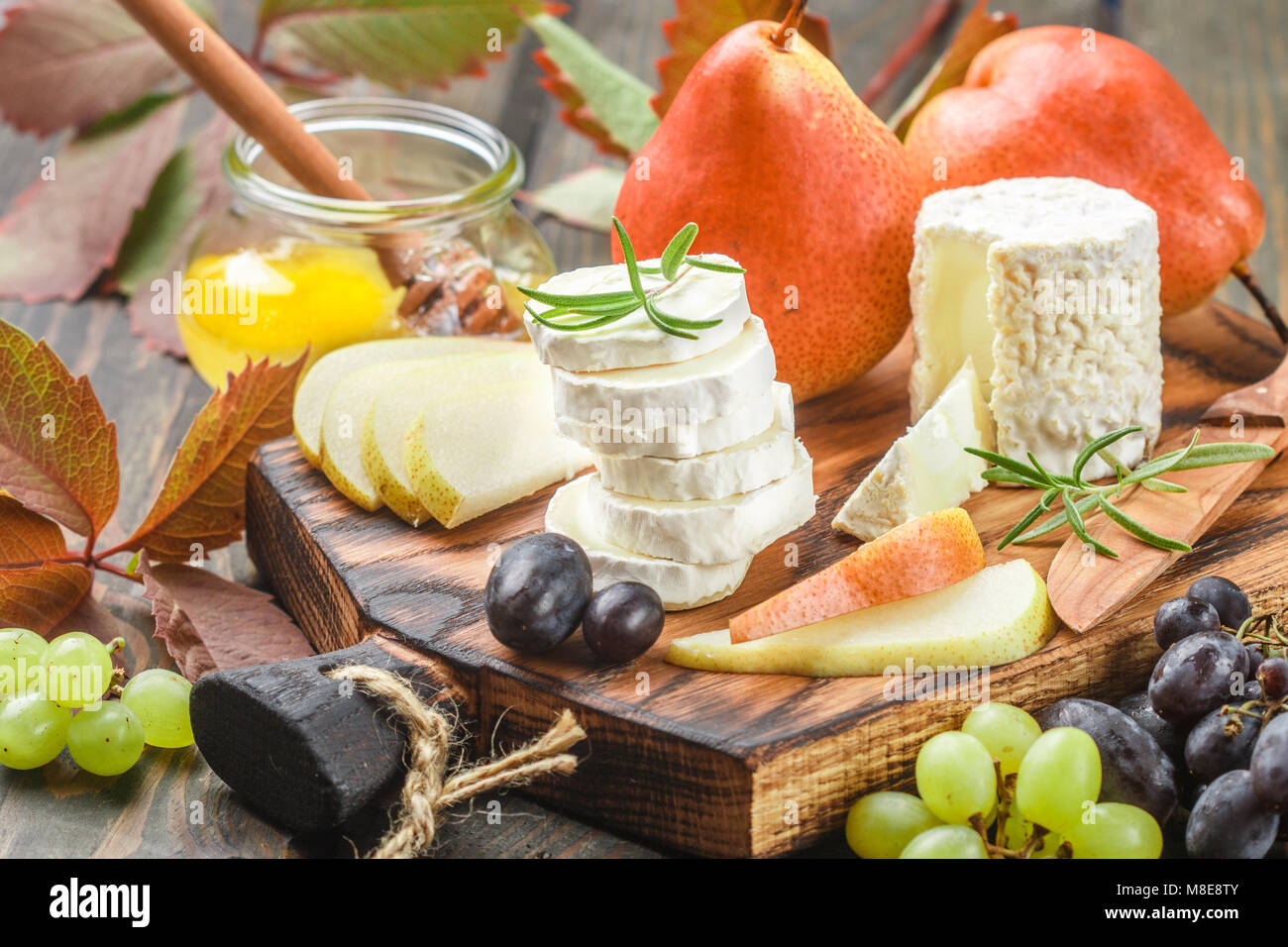 Goat cheese with fruit and honey. Camembert. Bree. Grape, pear and rosemary. Gourmet wine snacks. Selective focus Stock Photo