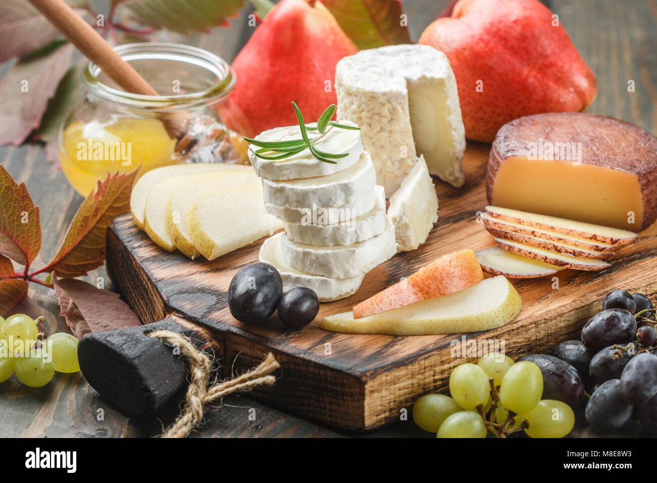 Set of fine cheeses with fruit and honey. Camembert. Bree. Grapes, pears and rosemary. Wine snacks for foodies. - Stock Image