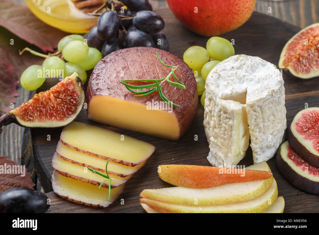 Set of fine cheeses with fruit and honey. Camembert. Bree. Grapes, figs, pears, and rosemary. Wine snacks for foodies. - Stock Image