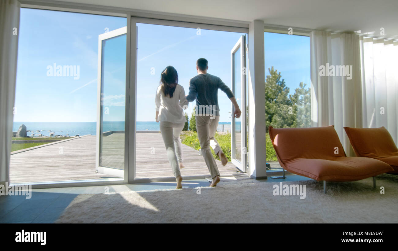 Happy Young Couple Holding Hands  Runs out of Their Home onto the Terrace with the Seaside View. - Stock Image