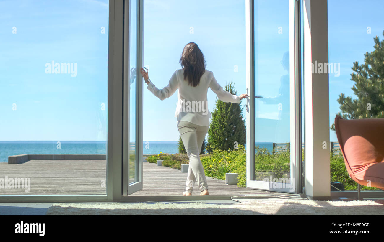 Shot of a Beautiful Brunette with Loose Hair Opening Doors of the Balcony and Walking onto Sunny Terrace with Seaside - Stock Image