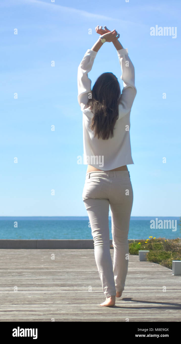 Shot of a Beautiful Brunette with Loose Hair Opening Doors of the Balcony and Walking onto Sunny Terrace with Seaside Stock Photo
