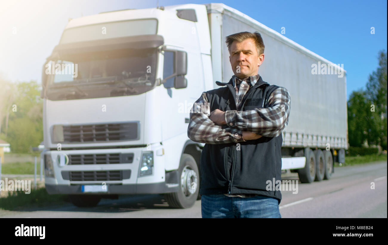 Professional Stands in the Middle of the Road and Proudly Crosses Arms. On the backgroud Parked White Semi Truck Stock Photo