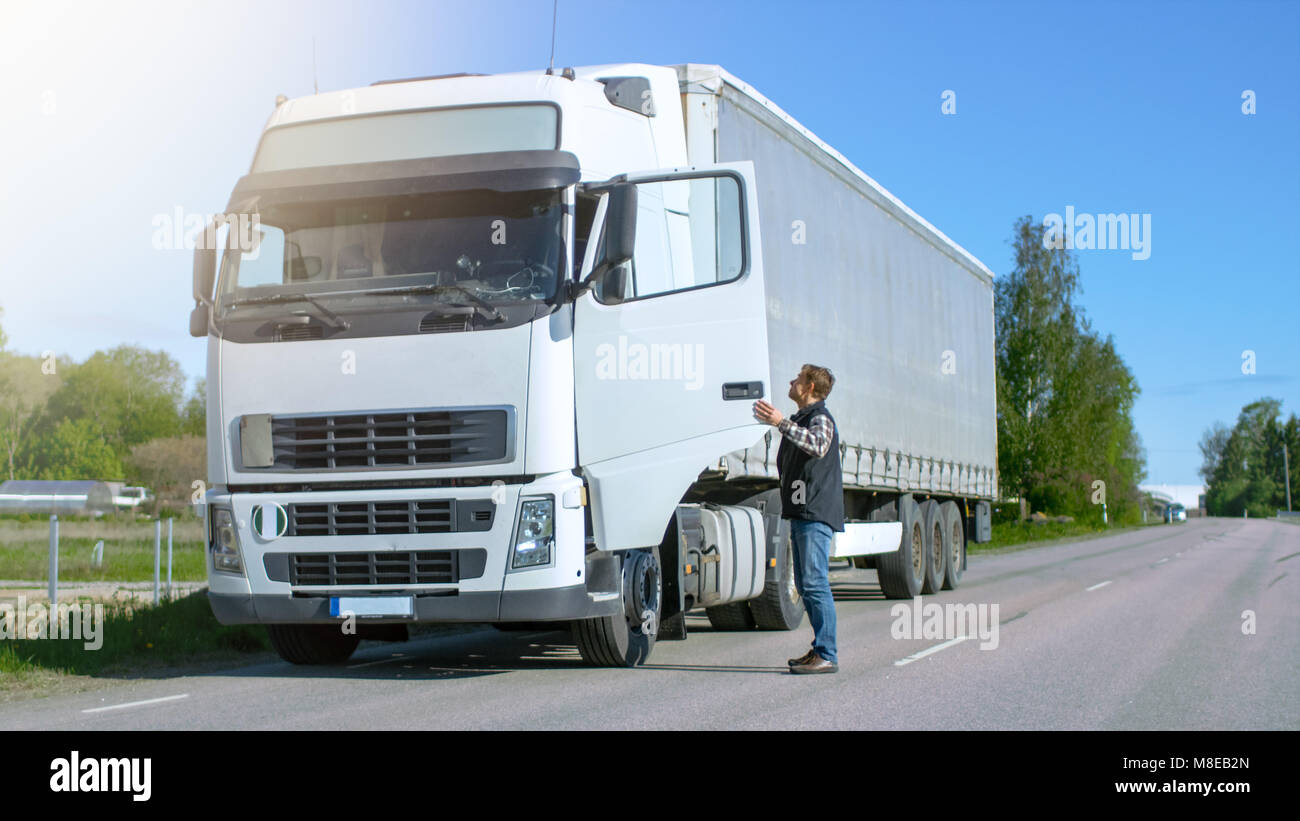 Truck Driver Gets out of His Parked White Cab-Over Truck. Day is Sunny, Driver is Professional. - Stock Image
